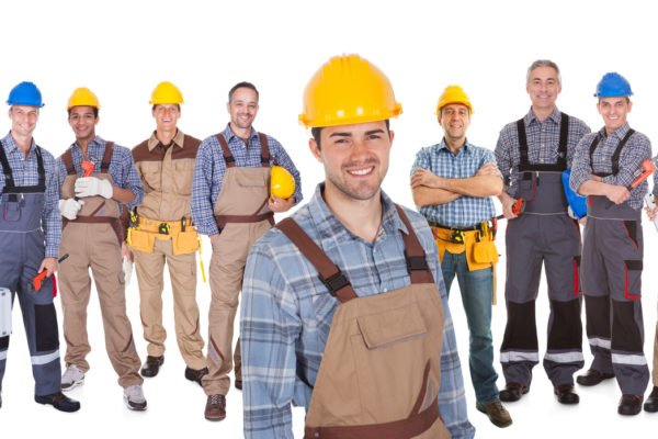 Portrait of happy construction worker with colleagues standing over white background